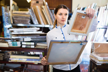 Woman is choosing new picture for her home in the store.