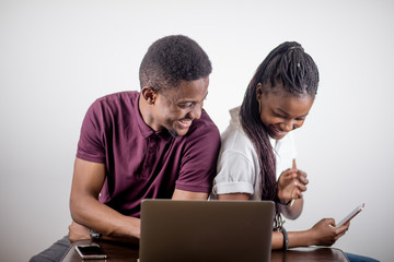 African couple. black girl sitting in front of laptop lookin at screen and laughing