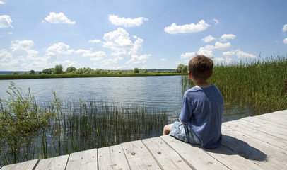 Boy Sitting On Pier Near Lake