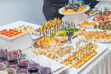 Catering table with food dishes, snacks and alcoholic and non-alcoholic drinks for guests of the event. Service at business meeting, party, weddings. Selective focus.