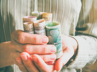 Arab dirhams. Curled banknotes in his hands.