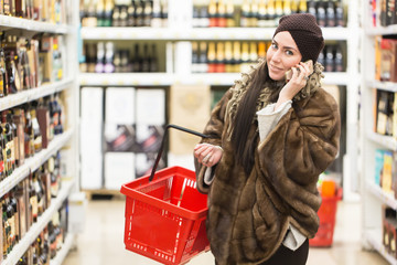 Shopping concept. Woman speaking phone and holding red shopping basket in the supermarket store near wine bottles windows.