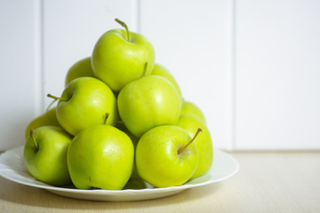 Green apples on a plate on a wooden table.