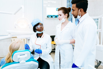Multiracial dental team with patient in dental clinic. Dental health concept.