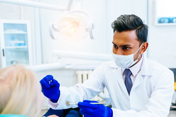 young confident asian male dentist Medical treatment to a female patient at the clinic. Dental clinic concept.