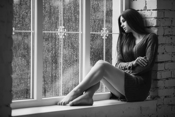 Beautiful young woman sitting alone near window with rain drops. Sexy and sad girl with long slim legs. Concept of loneliness. Black and white.