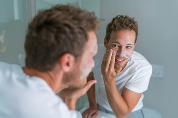 Man washing face with soap scrubbing exfoliation mask facial treatment looking in the mirror. Men taking care of skin, morning face wash routine for cleaning acne pimples.