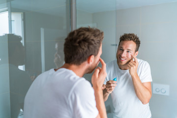 Happy young man taking care of his undereye wrinkles putting anti-aging eye cream.