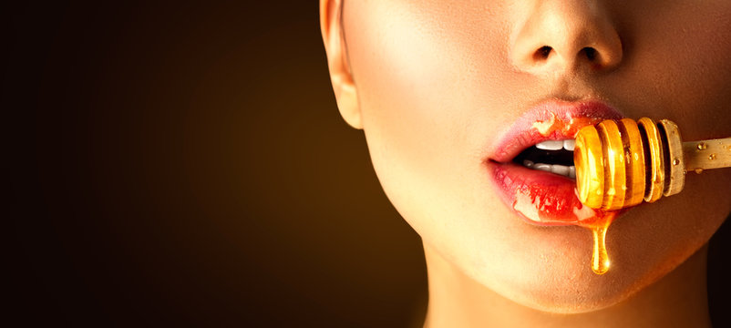 Honey dripping on sexy girl lips from the wooden spoon. Beauty model woman eating honey