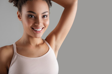 Close up of smiling woman in lingerie showing depilated armpit. Copy space on right side. Isolated on background
