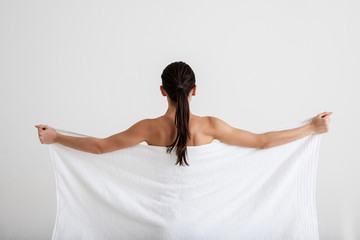 Calm woman taking care of her skin. She is hiding fit naked body under soft towel. Focus on back. Isolated on background
