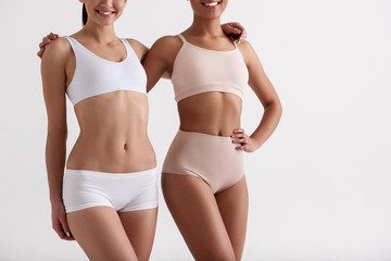 Two female friends leading a healthy lifestyle. They are wearing underwear and smiling. Isolated on background