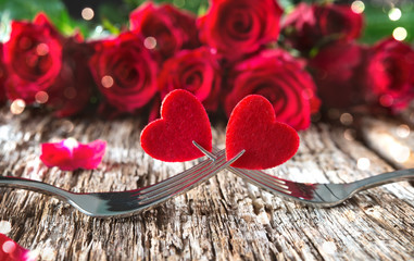 Hearts on forks in front of red roses