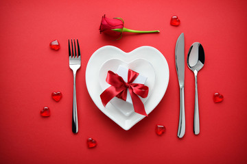 holidays table setting with a gift box on red background