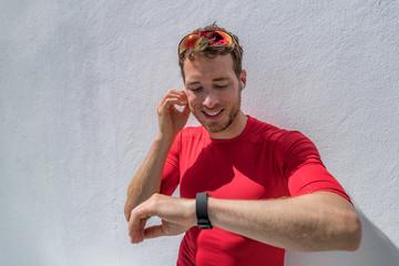 Smartwatch fitness athlete wearing watch and in-ear wireless earphones for music listening via bluetooth on smart technology wearable device. Triathlete man sports.