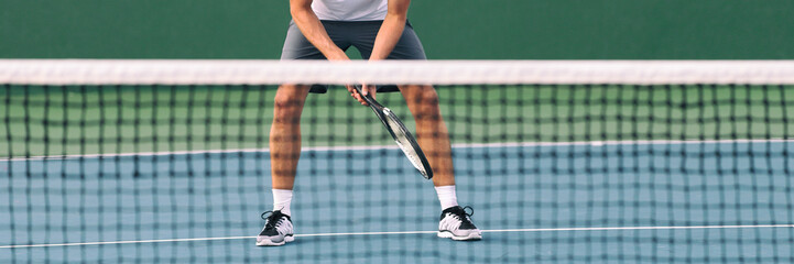 Tennis ready position male athlete player waiting for volley serve at net on blue hard court banner crop. Closeup of feet and legs standing waiting.