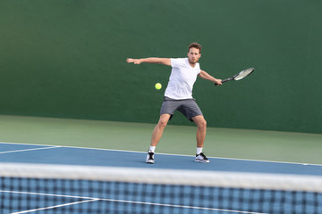 Professional tennis player athlete man focused on hitting ball over net on hard court playing tennis match with someone. Sport game fitness lifestyle person living an active summer lifestyle.