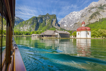 Traditional passenger boat on Königssee lake with famous St. Bartholomä pilgrimage chapel in summer, Bavaria, Germany