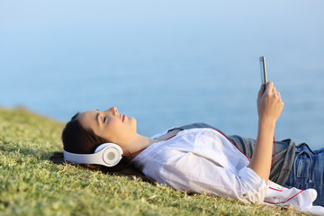 Woman relaxing listening to music on the grass