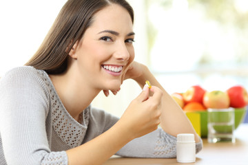 Woman taking a vitamin pill and looking at you at home