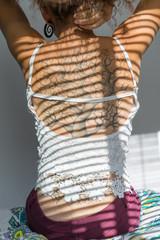 Tattooed woman posing in sunlight