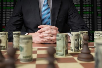 Investment strategy concept. Man is playing chess with money.