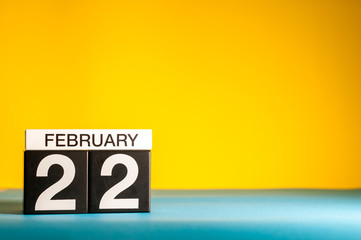 February 22nd. Day 22 of february month, calendar on yellow background. Winter time. Empty space for text