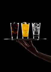 Hand holds tray with glass of cola orange water