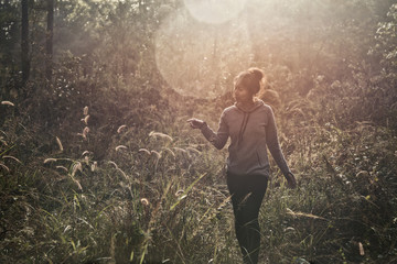 A young woman walking trekking through a green path in forest mountain summer sunrise thailand.