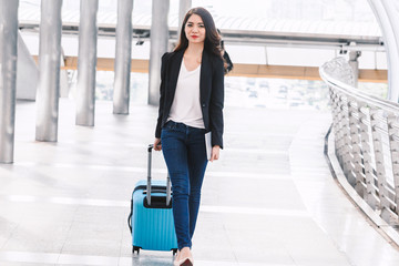 Happy successful businesswoman walking with luggage