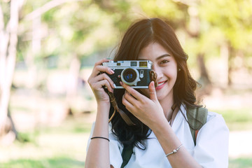 Asian woman taking picture with camera in park