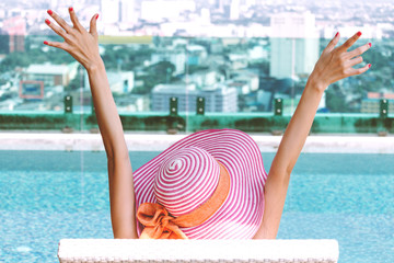 Woman sitting in swimming pool on summer vacation relaxing at resort spa