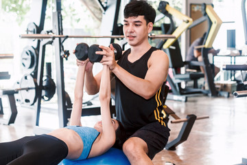 Handsome trainer and fitness woman with weight training equipment at  the gym.fitness and lifestyle concept