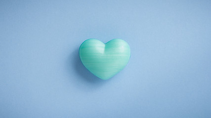 Turquoise heart shape over blue table. Romantic Valentine Day concept with copy space