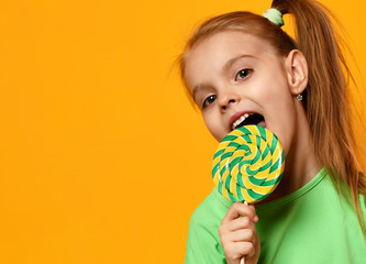 Happy young little child girl kid bite sweet lollypop candy
