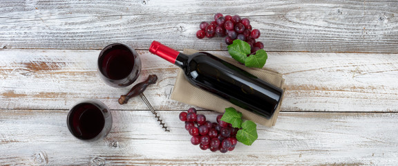 Red wine ready to drink with full bottle and grapes on white weathered wooden boards