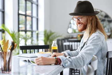Cheerful bearded male guy in stylish denim jacket, hat and eyewear reads magazines while sits at kitchen table, going to have lunch, reads very funny article. Hipster guy enjoys free time, reads