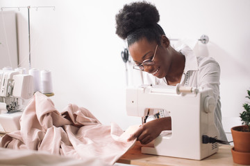 african seamstress sews clothes. Workplace of tailor - sewing machine, rolls of thread, fabric, scissors.