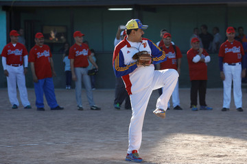 Venezuela's President Maduro throws the ball during a softball game with ministers and military high command members in Caracas