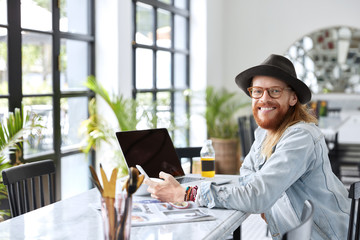 Bearded cheerful creative male with happy expression has breakfast in nearest cafe, recieves good news on cell phone, sits in front of opened laptop with copy blank screen, uses wireless wifi
