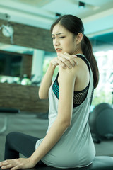 Woman touching her neck with hands while exercise. Young asian woman feel pain in her neck.