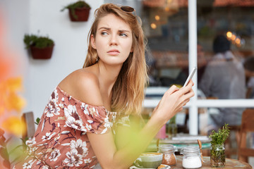 Thoughtful cute woman sits with cup of coffee against cafe interior, uses wireless internet for checking email or surfing internet, being bored to wait friend long time. People, modern urban lifestyle