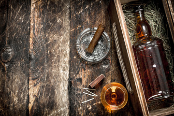 Cognac background. A bottle of cognac in a box with a glass and a cigar.