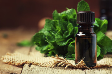 Essential oil of peppermint in a small brown bottle with fresh green mint, rustic style, vintage wooden background, selective focus