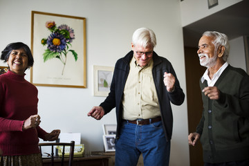 Senior people dancing together in a living room