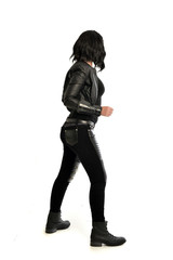 full length portrait of black haired girl wearing leather outfit. standing pose  view from behind, on a white background