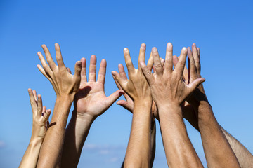 Group raising hands against blue sky background, close up