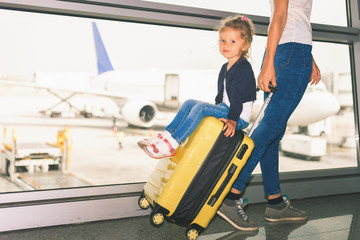 Mom carries your luggage with happy baby at airport terminal.