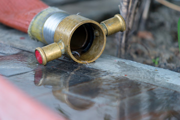 water flows out of Fire hose with reflection in water on the rough ground after use