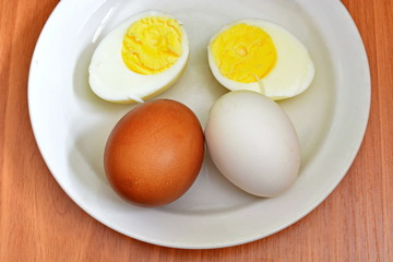 Half hard boiled chicken egg and whole red and white egg in eggshell on a white saucer and wooden table